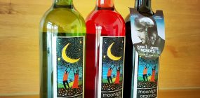"""Jeweils eine Flasche Stellar Moonlight Wein in Weiß, Rosé und Rot mit einem Flaschenanhänger des Filmes """"Die dunkle Seite des Mondes"""""""