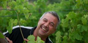 Der Winzer Rémy Soulié steht lachend inmitten seiner Reben