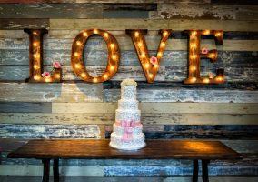Hochzeitstorte und das Wort Love in Leuchtbuchstaben